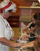 Mrs. Claus help children roll out dough